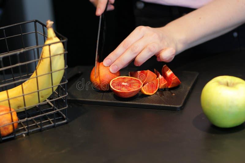 Cortar diversas frutas con un cuchillo La acción de las manos Naranja roja, plátanos, manzanas Fondo oscuro foto de archivo