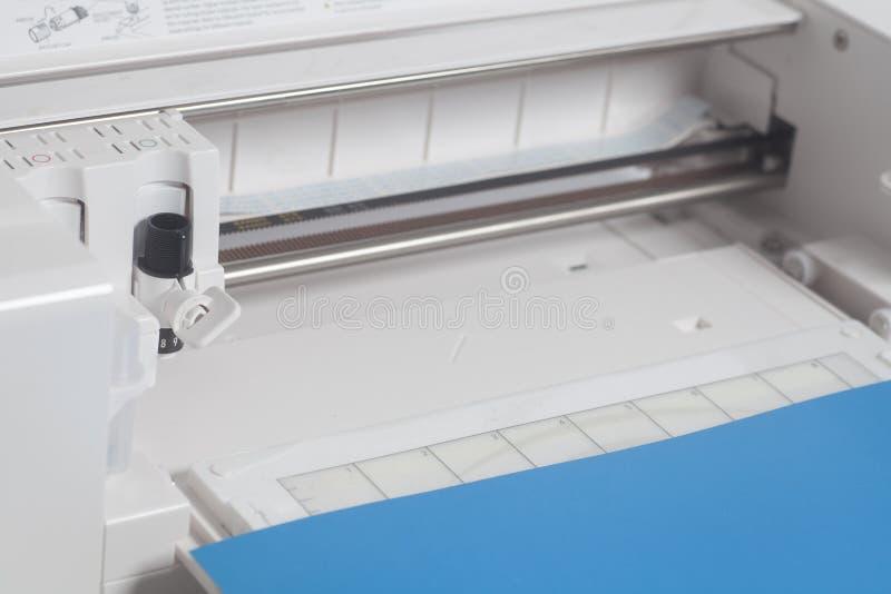 Cortar el trazador con el papel azul fotos de archivo libres de regalías