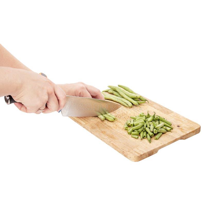 Cortar habas verdes frescas en una tabla de cortar en una tabla fotos de archivo