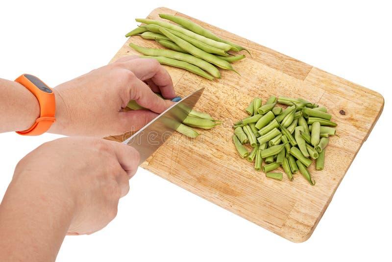 Cortar habas verdes frescas en una tabla de cortar en una tabla imágenes de archivo libres de regalías