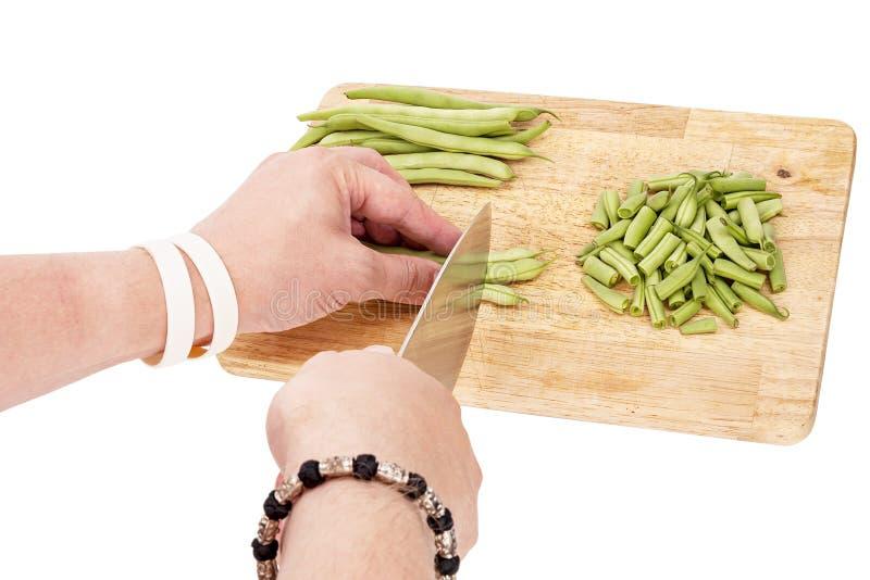 Cortar habas verdes frescas en una tabla de cortar en una tabla foto de archivo