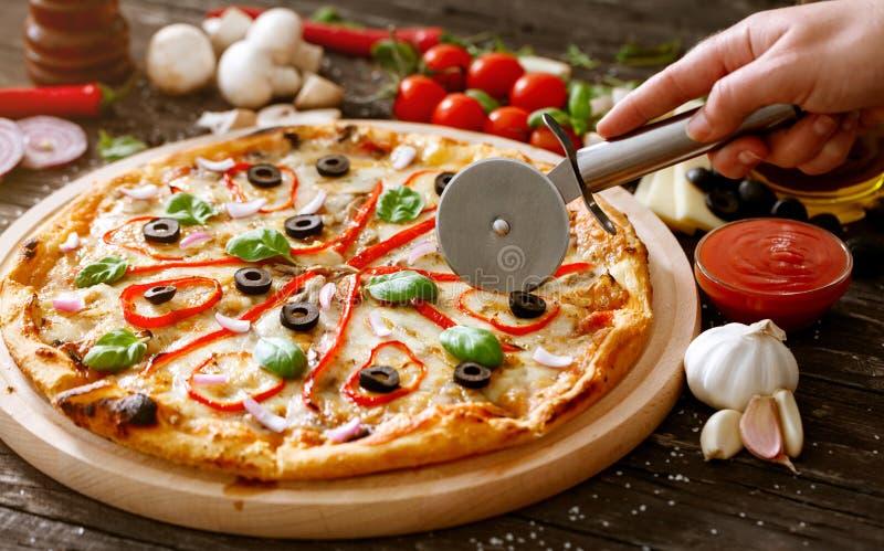 Cortar la pizza con el cortador de la pizza imágenes de archivo libres de regalías