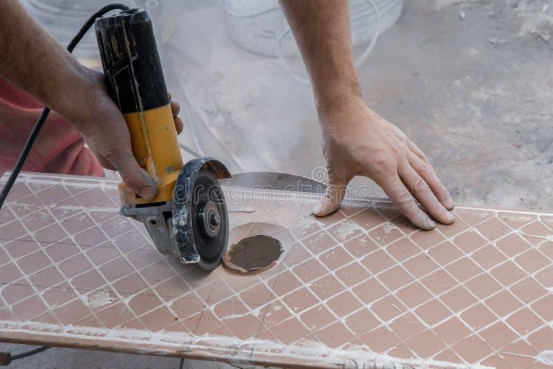 Cortar las baldosas cerámicas Un trabajador coloca una teja grande en una máquina foto de archivo