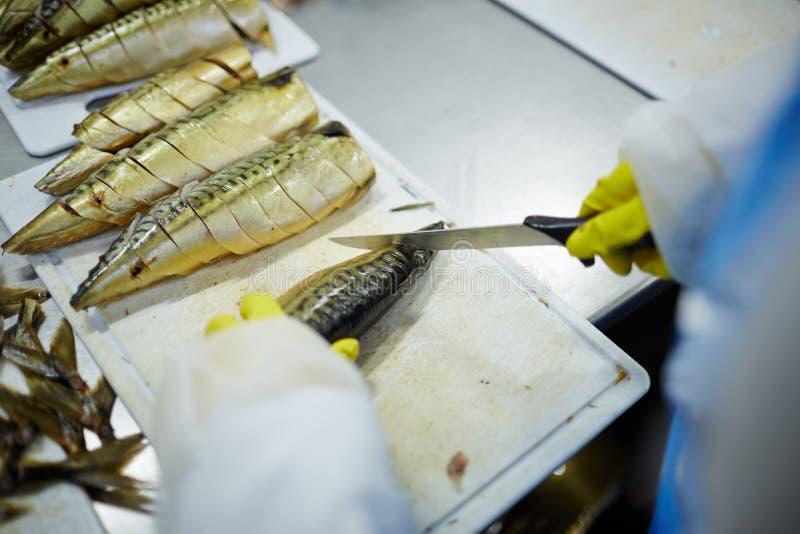 Cortar las sardinas imagenes de archivo