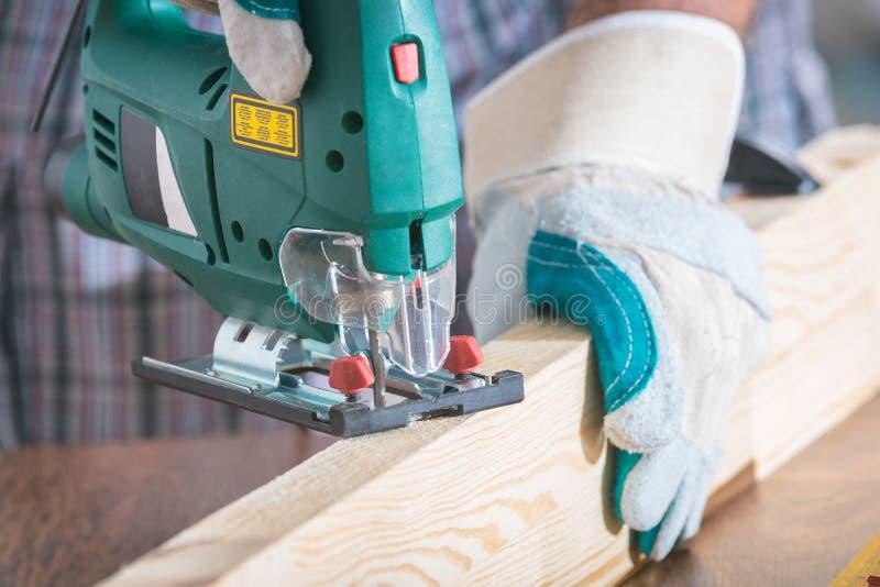 Cortar un pedazo de madera usando un rompecabezas imagenes de archivo