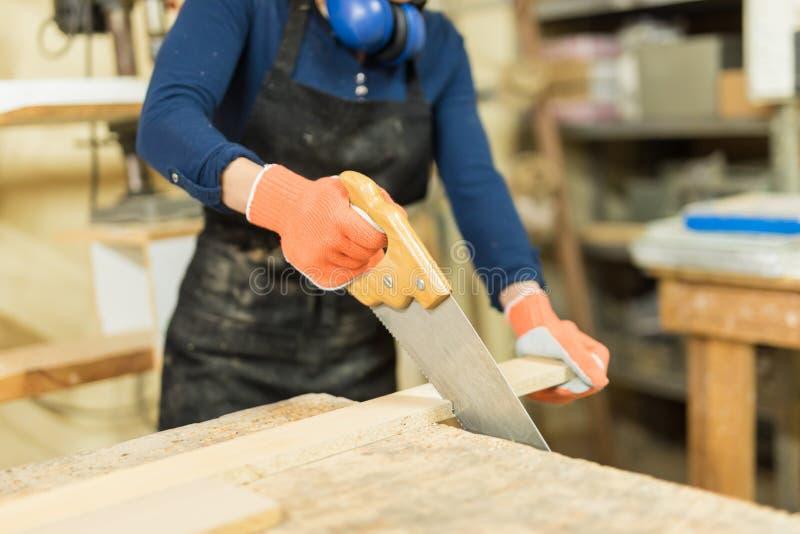 Cortar un poco de madera con una sierra de la mano fotografía de archivo libre de regalías