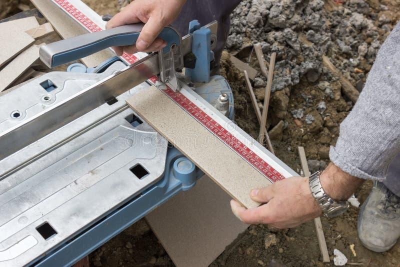 Cortar una teja grande con la herramienta de corte foto de archivo