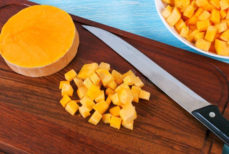 Corte a abóbora em uma placa de corte com uma faca fotografia de stock