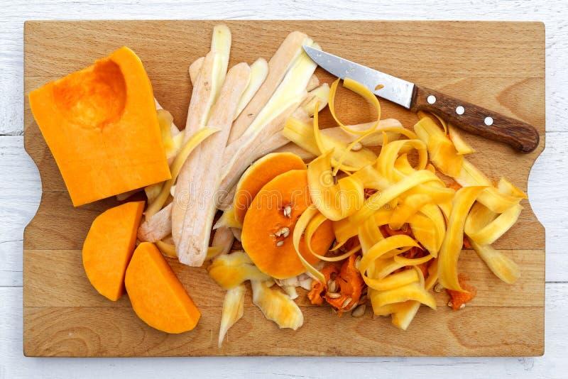Corte acima a polpa de butternut com cascas e faca no chopp de madeira marrom foto de stock