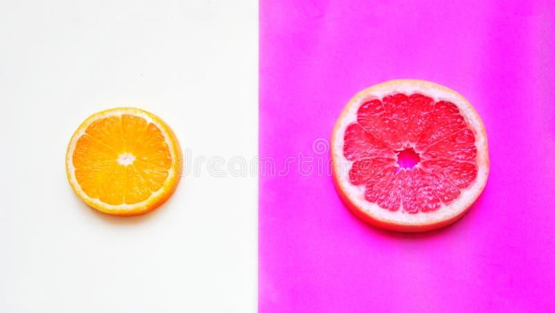 Corte alaranjado redondo em um fundo branco e em uma toranja cor-de-rosa redonda em um fundo lilás, dividindo-se ao meio imagens de stock
