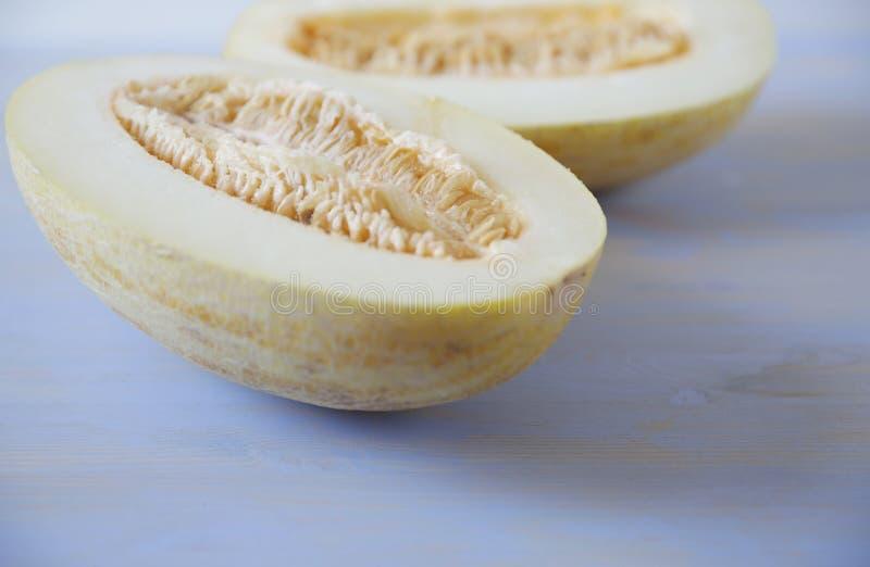 Corte amarelo maduro orgânico do melão doce ao meio isolado em um fundo de madeira azul branco foto de stock