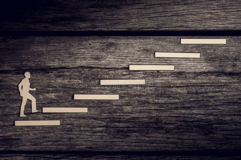 Corte as saídas do homem de papel que escalam as etapas ao sucesso fotos de stock