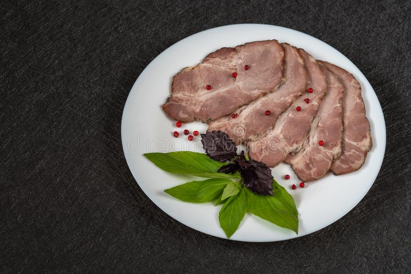 Corte cozido da carne em partes em uma placa branca com opinião superior do close-up das grões da manjericão e da pimenta vermelh fotos de stock royalty free