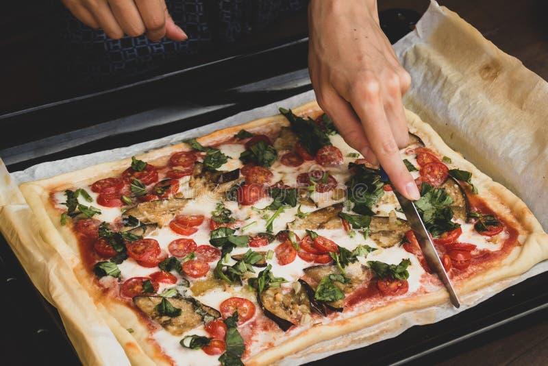 Corte da mulher pela forma retangular da faca e pela pizza feito à mão dos romana grossos close up italiano tradicional do marghe imagem de stock
