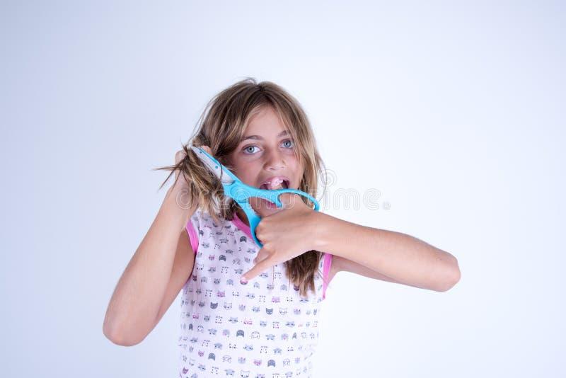 Corte de la muchacha su pelo con las tijeras imágenes de archivo libres de regalías
