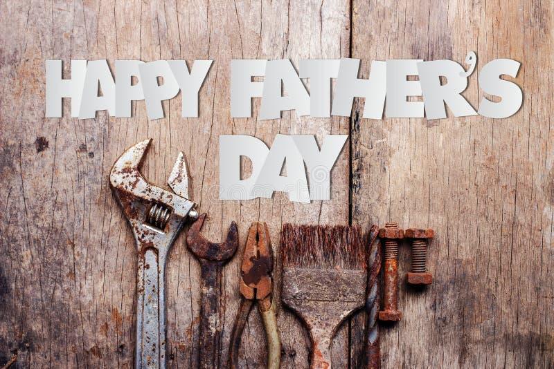 Corte de papel do texto feliz do dia de pai com as ferramentas oxidadas velhas no fundo de madeira fotos de stock
