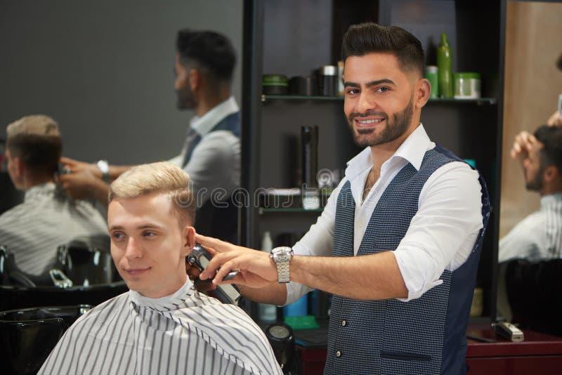 Corte de pelo hermoso del ` s del cliente del ajuste del peluquero, mirando la cámara y la sonrisa imagenes de archivo