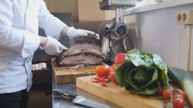 Corte de uma grande parte de carne fumado em uma placa de madeira fotos de stock royalty free
