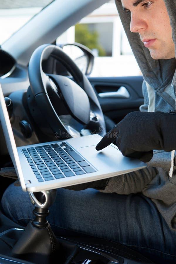 Corte de Using Laptop To do ladrão no software de segurança do carro foto de stock royalty free