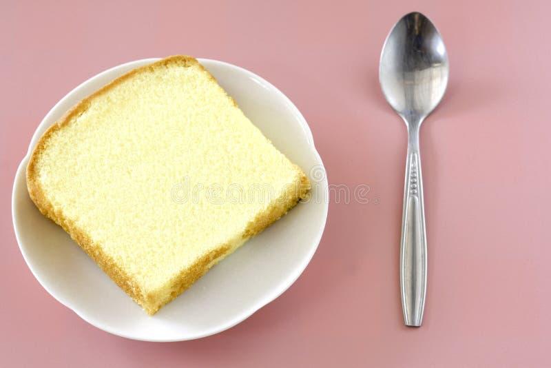 Corte del cuadrado de la visión superior de la torta de la mantequilla de la vainilla en el plato blanco en fondo rosado fotos de archivo