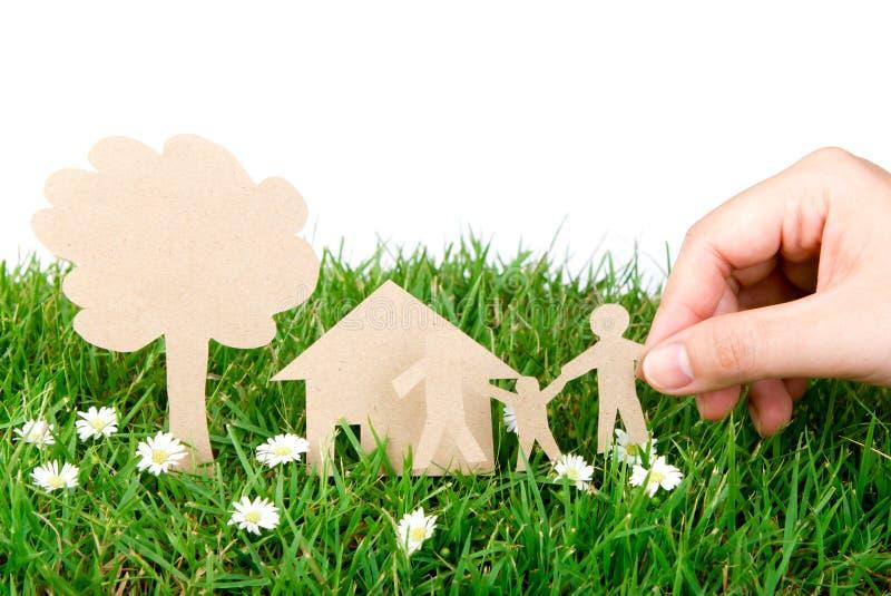 Corte del papel del asimiento de la mano de la familia sobre hierba verde. imagen de archivo libre de regalías