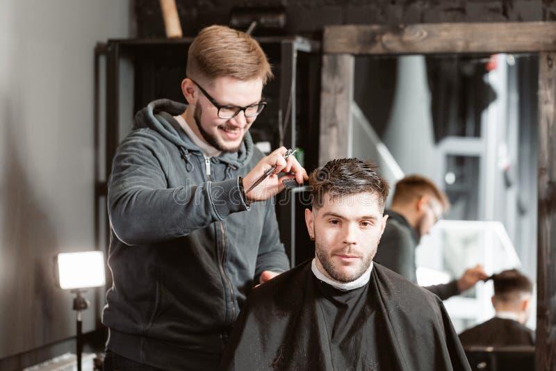Corte del pelo con las tijeras del metal El pelo de los cortes y la barba principales de los hombres en la barber?a, peluquero ha fotografía de archivo
