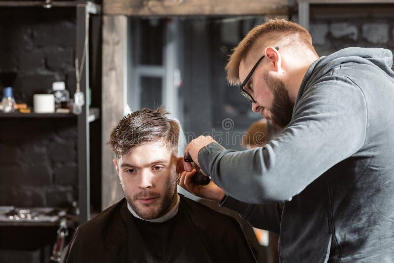 Corte del pelo con las tijeras del metal El pelo de los cortes y la barba principales de los hombres en la barber?a, peluquero ha fotos de archivo
