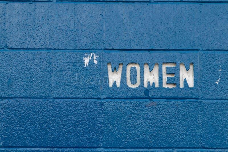 Corte del texto de la mujer blanca en los bloques de cemento azules fotografía de archivo libre de regalías