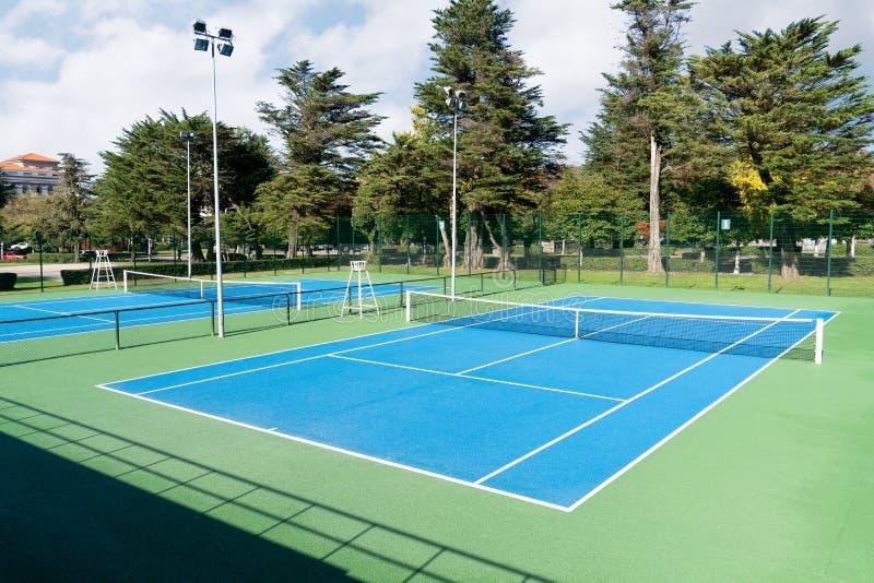 Corte di tennis blu giorno soleggiato all'aperto Paesaggio di sport fotografie stock