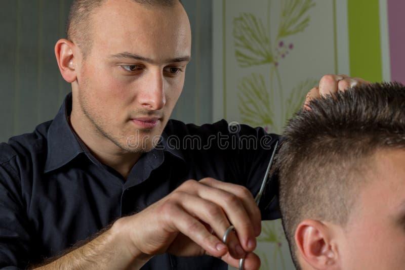 Corte do cabelo dos homens com tesouras em um salão de beleza fotos de stock