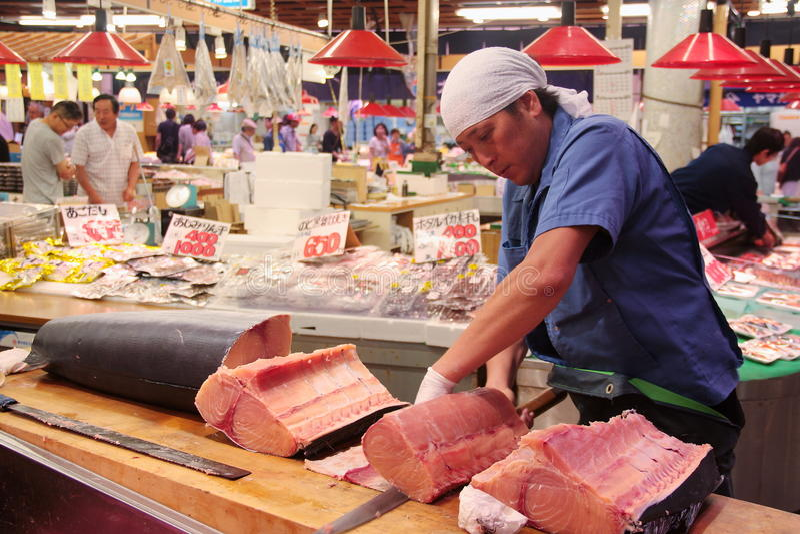 Corte do comerciante e carne filetting do espadarte OMI-cho no mercado Kanazawa Japão fotografia de stock