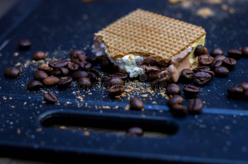 Corte do gelado da baunilha, do chocolate e do creme ao lado dos waffles e dos feijões de café imagens de stock royalty free