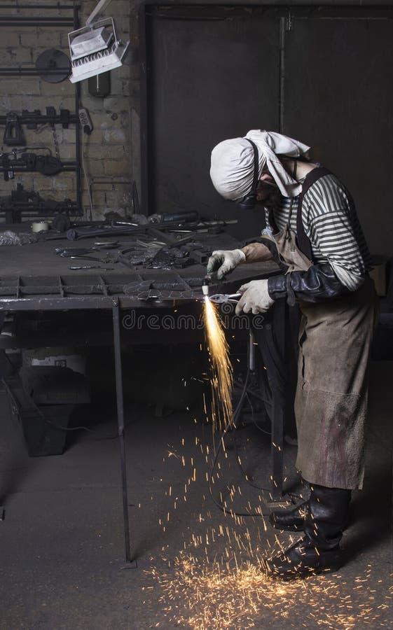 Corte do metalúrgico na placa de aço que cria as faíscas, cortando o ferro foto de stock