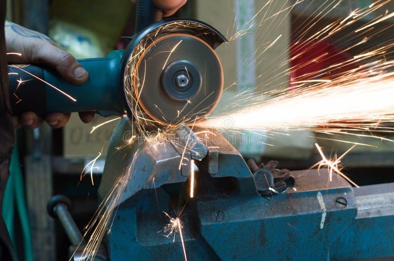 Corte do metal com uma máquina de moedura com faíscas foto de stock royalty free