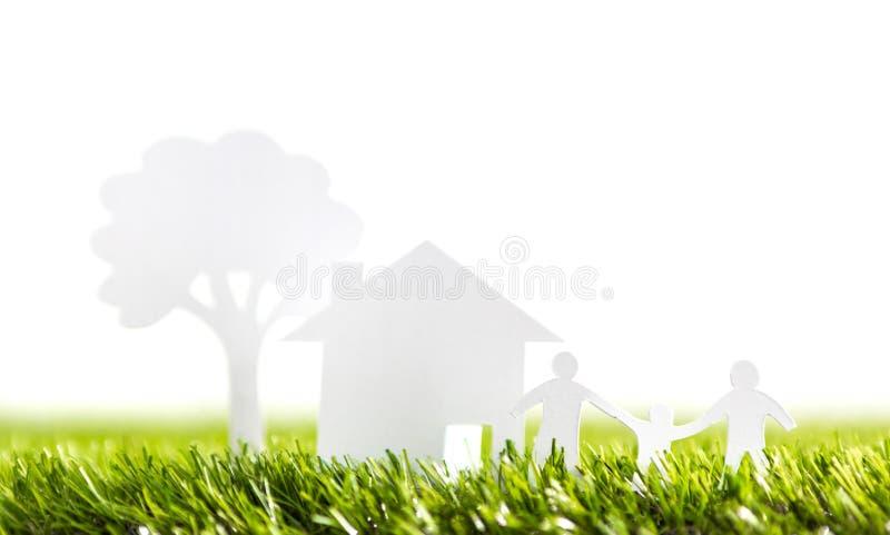Corte do papel da família com casa e da árvore na grama imagens de stock royalty free