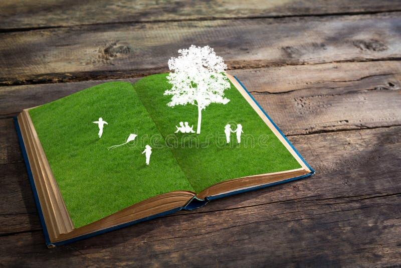 Corte do papel do jogo de crianças na grama da grama verde imagens de stock