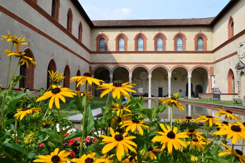 Corte ducale del castello di Sforza a Milano e le sue gallerie medievali antiche, riflessa nell'acqua dello stagno immagine stock libera da diritti