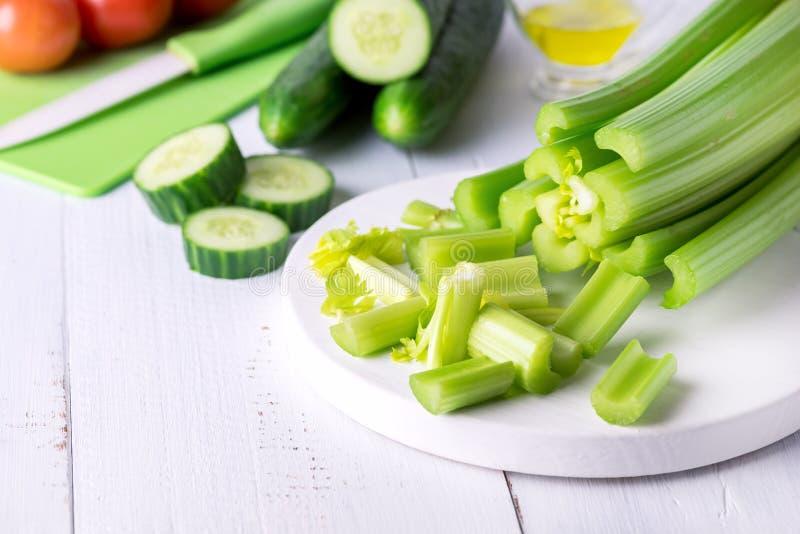 Corte el apio fresco maduro en las verduras blancas del pepino de la comida de la dieta sana de la tabla de cortar foto de archivo