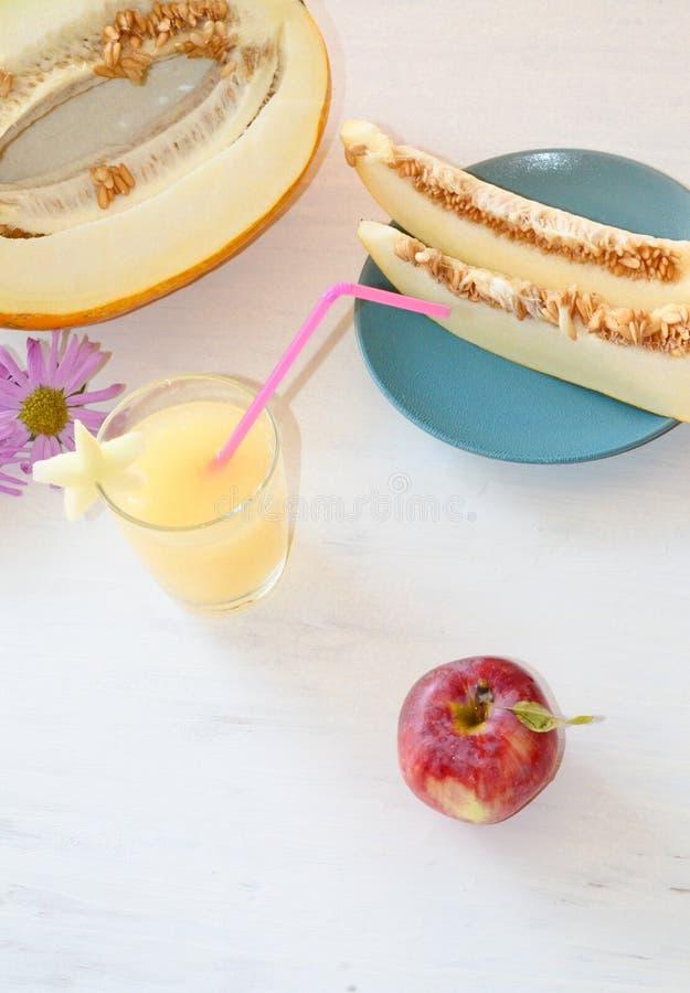 Corte el melón al lado de un vidrio del smoothie con una rebanada de melón la estrella de la paja cerca de todos en fondo blanco  foto de archivo