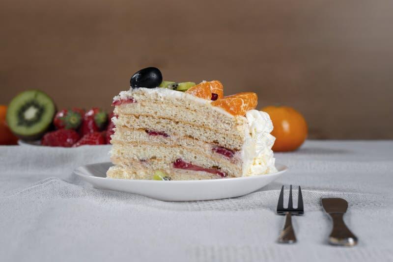 Corte el pedazo de torta hecho de los ingredientes naturales, de la fruta de kiwi fresca, de las uvas, de la mandarina y de sopor fotografía de archivo