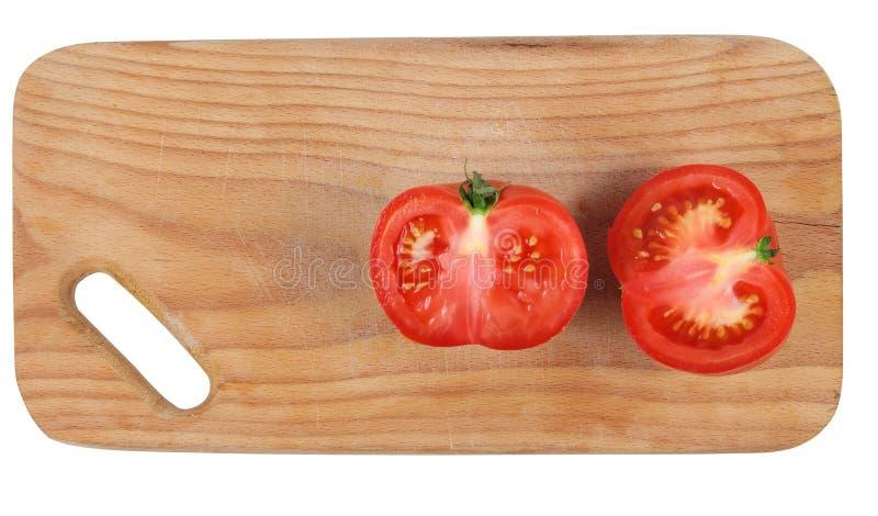 Corte el tomate en tarjeta de la cocina. imagen de archivo