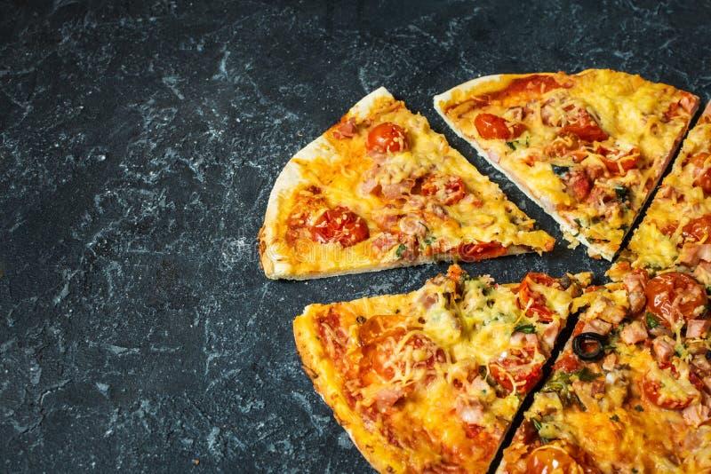 Corte fatias em deliciosas a pizza fresca com tomates e azeitona em um fundo escuro Vista superior Pizza na tabela preta imagem de stock