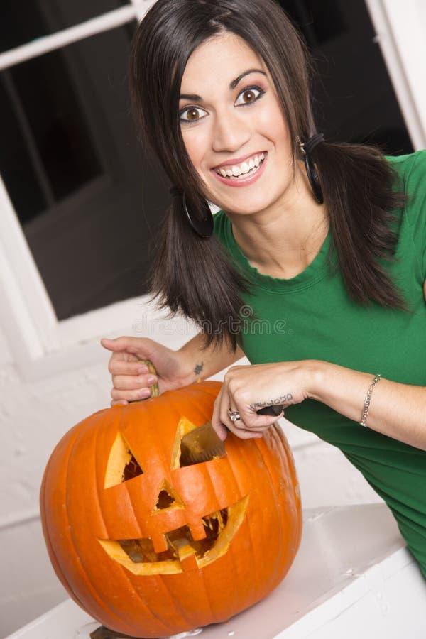 Corte feliz emocionado de la mujer que talla la linterna de la calabaza de Halloween imagenes de archivo