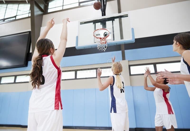 Corte femenina de Team Shooting At Basket On del baloncesto de la High School secundaria fotos de archivo libres de regalías