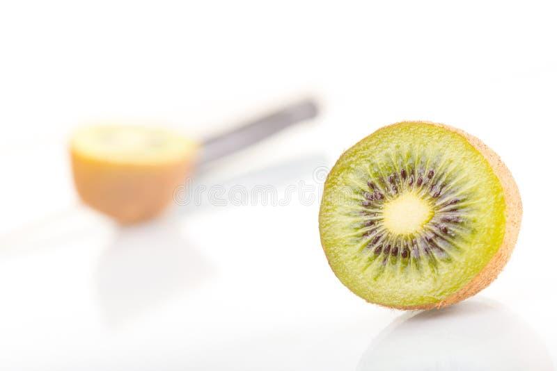 Corte fresco verde de la fruta de kiwi en mitad y cuchillo en un fondo blanco foto de archivo