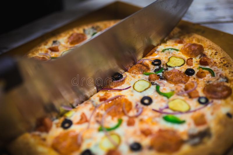 Corte grande apetitoso de la pizza en los pedazos, mintiendo en el tablero con los n?meros que indican su di?metro el 16cm fotos de archivo