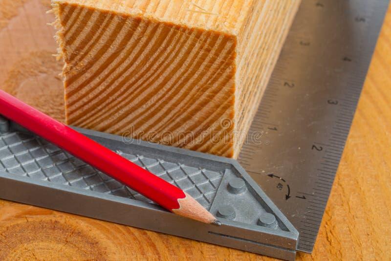Corte la madera con el cuadrado y el lápiz de intento imagen de archivo libre de regalías