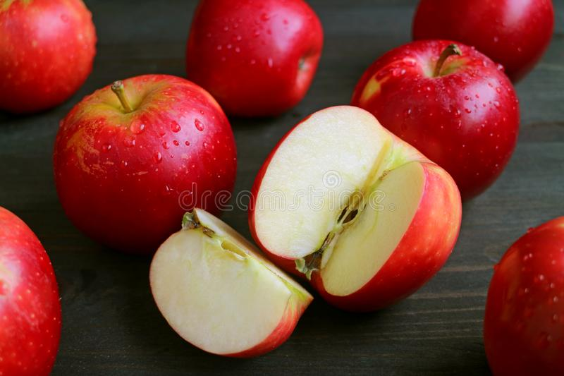 Corte la manzana roja madura fresca entre muchas frutas enteras con las gotitas de agua dispersadas en la tabla de madera marrón  fotografía de archivo libre de regalías