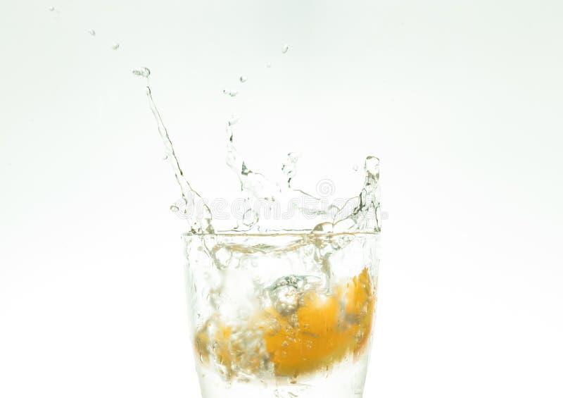 Corte la rebanada anaranjada en un vaso de agua y haga un espray en un fondo blanco espray de agua en el aire una parte de los de foto de archivo libre de regalías