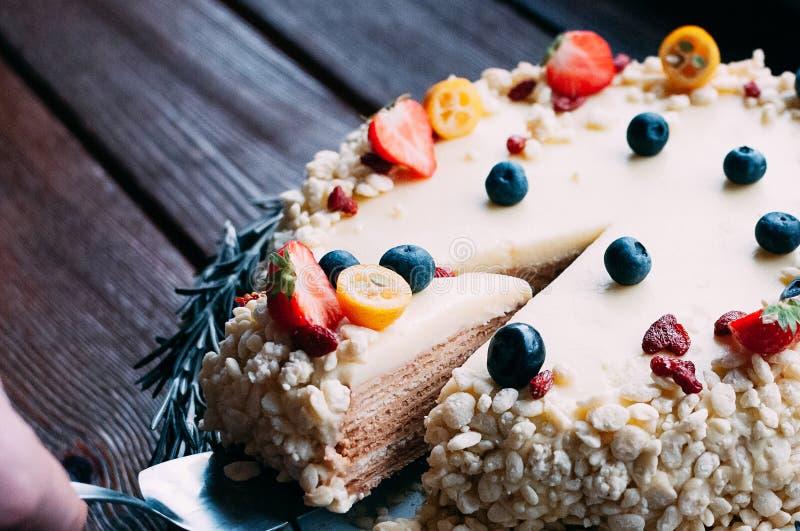 Corte la torta de chocolate blanca del pedazo con las bayas imagen de archivo